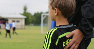 soccer coach with boy player