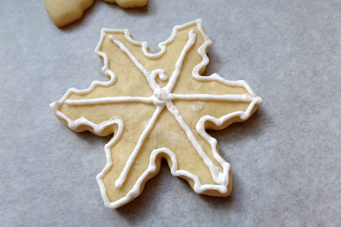 Icing a snowflake cookie
